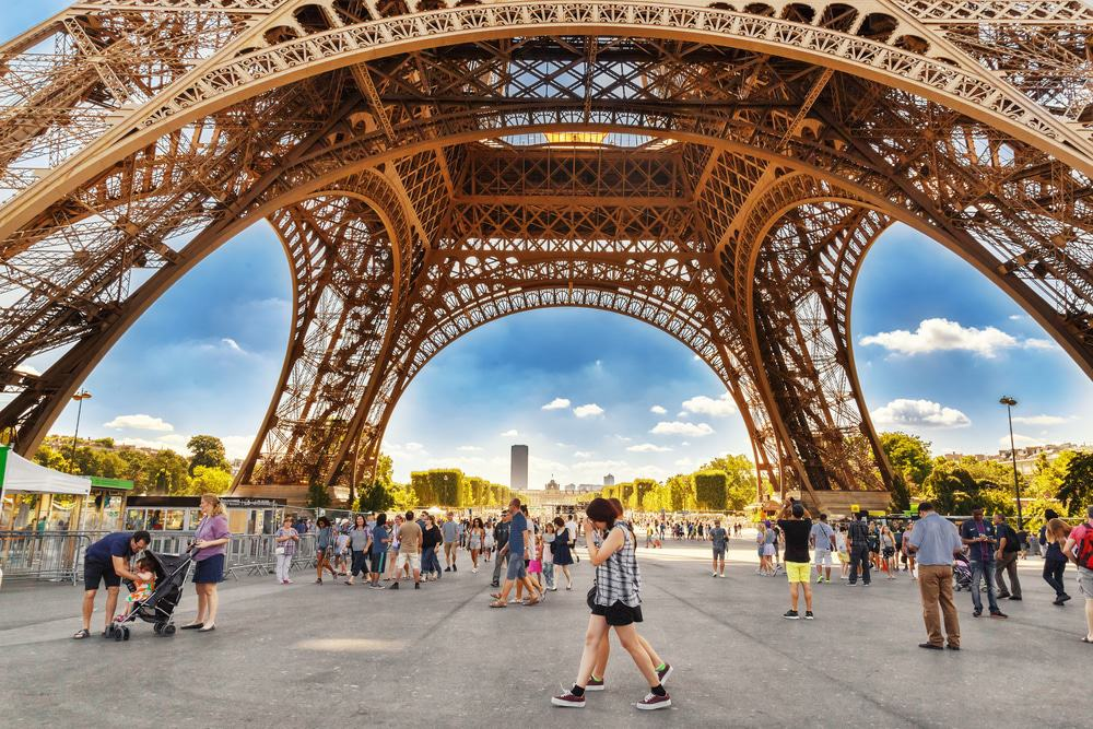 Tourists Walking under Eiffel Tower